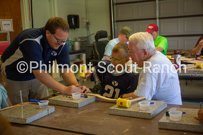 A father and grandfather help a boy hammer a leather stamp into a belt at the Philmont Training Center craft center at Philmont Scout Ranch in Cimarron, New Mexico on Monday, July 29. 2019.