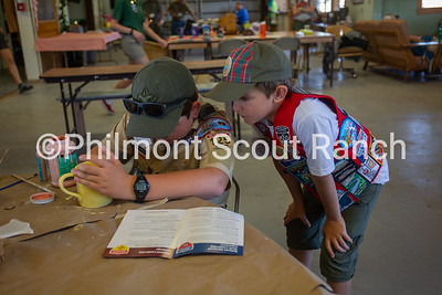 Quinn Dickinson watches Haldan Dickinson paint a ceramic mug at the Philmont Training Center craft center at Philmont Scout Ranch in Cimarron, New Mexico on Monday, July 29. 2019.