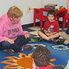 Staff photo by Cathy Spaulding<br /> Dr. Carol Ford sits on the floor to tell stories with her special education kindergarten students at Ben Franklin Science Academy. She was named Muskogee Public Schools Teacher of the Year on Friday.