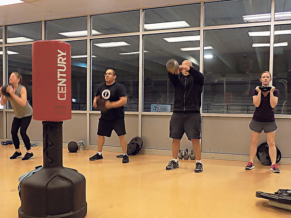 MIKE ELSWICK/Muskogee Phoenix<br /> Working with weights and kettle balls are part of the workout provided during a boxing cardio circuit training at the City of Muskogee Swim and Fitness Center.