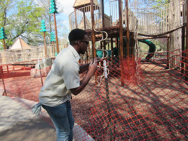 CATHY SPAULDING/Muskogee Phoenix<br /> Muskogee Parks and Recreation Department worker Chris Mims ties temporary fencing to a post Tuesday at the Honor Heights Park playground, which, along with restrooms, were closed to avoid the spread of COVID-19.