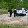 Staff photo by Wendy Burton<br /> Eufaula police officers and an employee of the state medical examiner's office talk briefly Monday after bringing skeletal remains out of the woods, which were found Sunday evening.