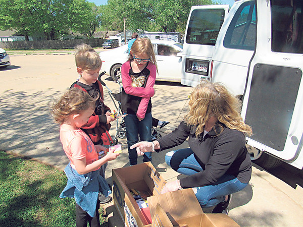 CATHY SPAULDING/Muskogee Phoenix <br /> Youngsters, from left, Mazeleigh Byrd, Wyatt Cox and Autumn Bishop, pick up school supplies on Friday from Whittier Elementary School Principal Lisa Rogers. The children walked to the school to get their curbside school lunches and supplies.