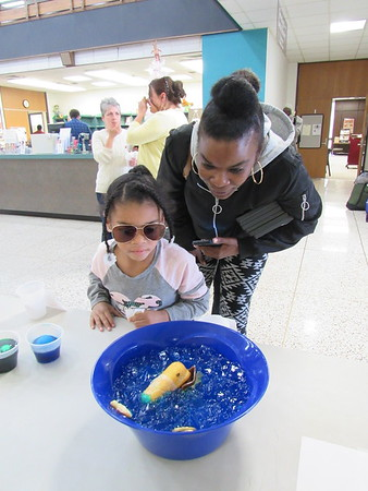 "CATHY SPAULDING/Muskogee Phoenix<br /> Mya Corell, 6, and her mother, Mona Vanhook-Correll<br /> study a gelatin and Twinkie display depicting the book ""Jaws"" at Muskogee Public Library. Visitors voted on their favorite culinary depictions of popular books Thursday. Exhibits included ""Silence of the Yams"" and ""Ketchup in the Rye."""