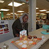 KENTON BROOKS/Muskogee Phoenix<br /> Kathleen Kirk of Muskogee sets up her entry at the Muskogee Public Library's Book Eats on Thursday. The<br /> event is part of International Edible Books Festival, and the public was invited to create an edible book. Kirk, a former Navy commander who moved from New Orleans in 2006, chose the book, 'If You Give A Moose A Muffin.' Her creation included vanilla wafers, pretzels and junior mints, chocolate icing and eyes made of candy.