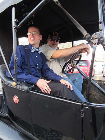 CATHY SPAULDING/Muskogee Phoenix<br /> Oklahoma School for the Blind student Conner Hilton, left, inspects his surroundings before riding to his prom in a 1914 Ford Model T driven by Cruis'n Angels member Larry Ross. The car club chauffeured OSB students to their prom Wednesday.