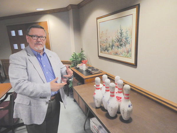 Staff photo by Mark Hughes<br /> Dr. Tim McElroy, Northeastern State University Muskogee campus dean, explains how old bowling pins will be used to help raise money for local education. More than 16 bowling teams representing various businesses and organizations have entered Junior Achievement's DiscoBowl fundraiser to be held April 27 at Green Country Lanes. Each team has to decorate a pin in the disco theme.