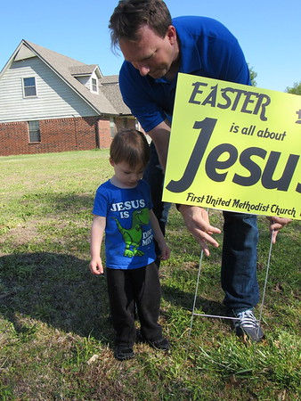 """Staff photo by Cathy Spaulding<br /> First United Methodist Church of Fort Gibson pastor, the Rev. Barry Collins, and his 2-year-old son, Thatcher, put up a sign proclaiming """"Easter is all about Jesus."""" Yard signs were put up all over Fort Gibson in preparation for Easter."""