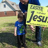 "Staff photo by Cathy Spaulding<br /> First United Methodist Church of Fort Gibson pastor, the Rev. Barry Collins, and his 2-year-old son, Thatcher, put up a sign proclaiming ""Easter is all about Jesus."" Yard signs were put up all over Fort Gibson in preparation for Easter."