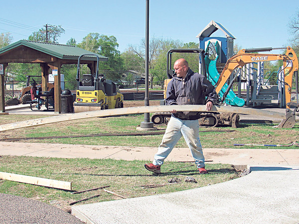 CATHY SPAULDING/Muskogee Phoenix<br /> Chris Malone of Builders Unlimited moves a frame from a new sidewalk at the Railroad Street Skate Park and Splash Pad. The town of Fort Gibson is erecting a new swing set featuring items for children with handicaps.