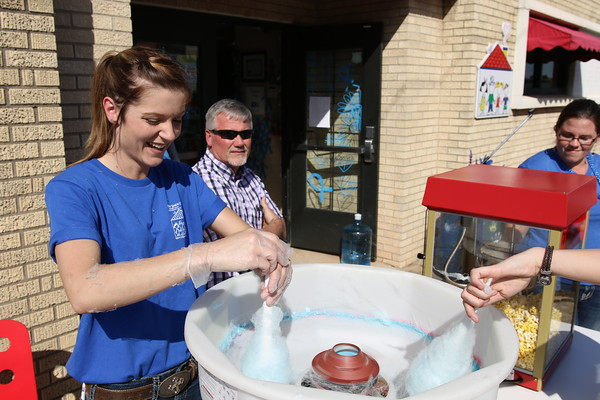 Staff photo by Harrison Grimwood<br /> Selena Rodden spins cotton candy, covering herself in the process, during the Child Abuse Prevention Block Party.