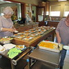 CATHY SPAULDING/Muskogee Phoenix<br /> Mildred Ewing, left, and Deb Smith fill meal containers at Presbyterian Church of Muskogee. The meals are delivered to homes of shut-ins.