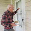 CATHY SPAULDING/Muskogee Phoenix<br /> Gordon Wallace knocks on a door to deliver a lunch. Lunches are delivered Wednesdays and Fridays.