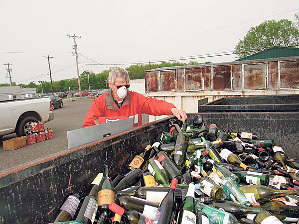 CATHY SPAULDING/Muskogee Phoenix<br /> William Dewel deposits bottles in a recycling bin. Muskogee's Recycle Drop-Off Center is seeing more activity with more people staying home.