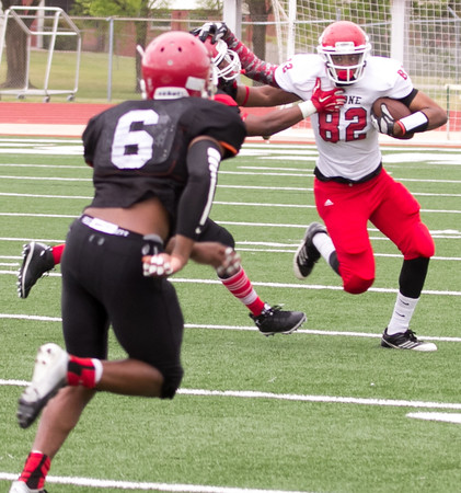 Special photo by Shane Keeter<br /> Cameron Ashley, right, stiff arms David Cooper as Jamarcus Darden, left, comes in to assist on Saturday during Bacone's annual spring football game on Creek Nation Field at Indian Bowl.