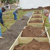 Staff photo by Mark Hughes<br /> Jean Lewis prepares one of the 4-by-8-foot raised beds for a community garden while Cedric Johnson and Sharon Champlin smooth out gravel for a walkway among the eventual 24 garden plots. The Grace Episcopal Church members built the plots Saturday on donated land at Seventh and Court streets.