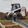 Staff photo by Mark Hughes<br /> Sharon Champlin rolls out plastic sheets on which gravel was shoveled to form pathways around the garden beds. At rear, Gary Ketcham operates a dirt mover.