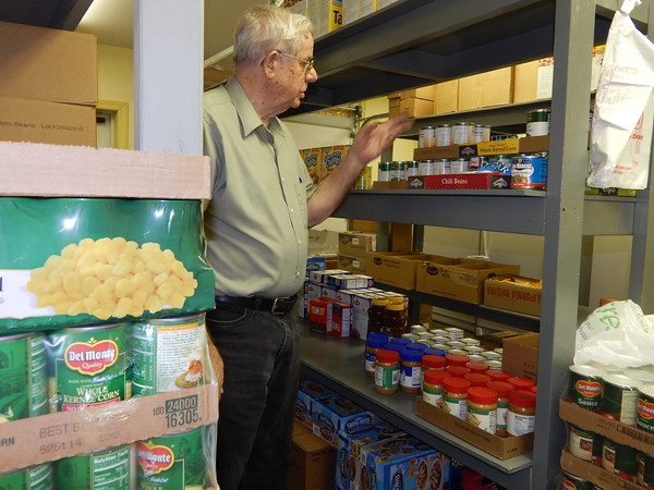 Staff photo by Cathy Spaulding<br /> Ed Falleur looks through food shelves at Catholic Charities, a Muskogee ministry he helped set up on West Broadway. He retired as its director last summer but continues to work there as a volunteer.