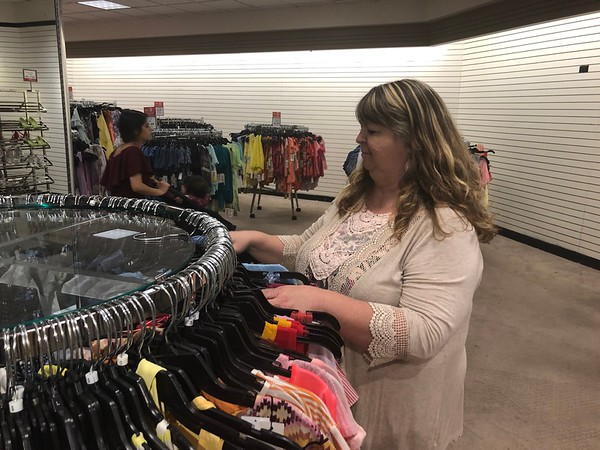 CHESLEY OXENDINE/Muskogee Phoenix<br /> Cynthia Acuff inspects a rack at Dillard's Muskogee, which closes May 4. Acuff has been with the store since its 1987 inception at Arrowhead Mall.