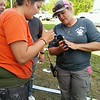 Staff photo by Wendy Burton<br /> Gina Wilson, left, and Fort Gibson Animal Control Officer Brooke Brown tend to a 6-day-old puppy just rescued after being trapped under a building away from its mother for three days.