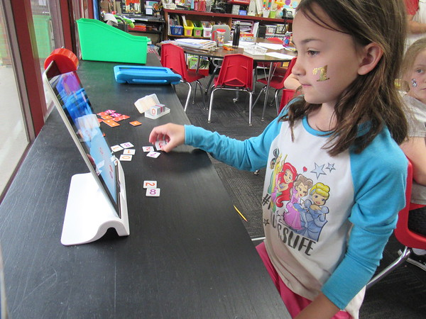CATHY SPAULDING/Muskogee Phoenix<br /> Second-grader Kinsleigh Weidel ponders what number to scan under an OSMO reader atop a tablet computer. A Fort Gibson Education Foundation grant helped the school obtain OSMO devices.