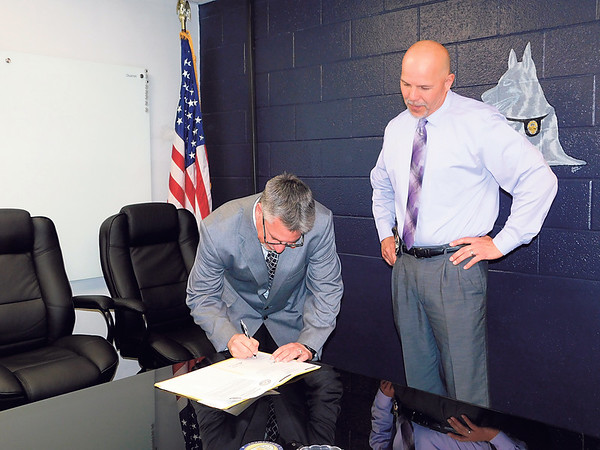 Kenton Brooks/Muskogee Phoenix<br /> Muskogee Police Chief Johnny Teehee watches Cherokee National Marshal Service Capt. Danny Tanner sign the memorandum of understanding between the two law enforcement agencies at the Muskogee Police Department. The memorandum gives the two agencies the ability to assist each other in their respective jurisdictions.