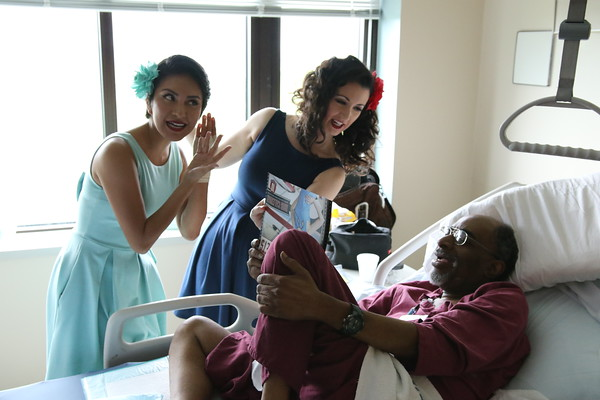 """Staff photo by Harrison Grimwood<br /> Pin-ups for Veterans models Gina Elise, left, and Valentina """"CiCi"""" Cahill, right, flirt with Navy veteran Thello L. White during their visit to the Jack C. Montgomery VA Medical Center."""