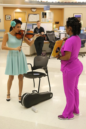 """Staff photo by Harrison Grimwood<br /> Pin-ups for Veterans model Valentina """"CiCi"""" Cahill, left, plays her violin for a group of veterans during her visit to the Jack C. Montgomery VA Medical Center."""