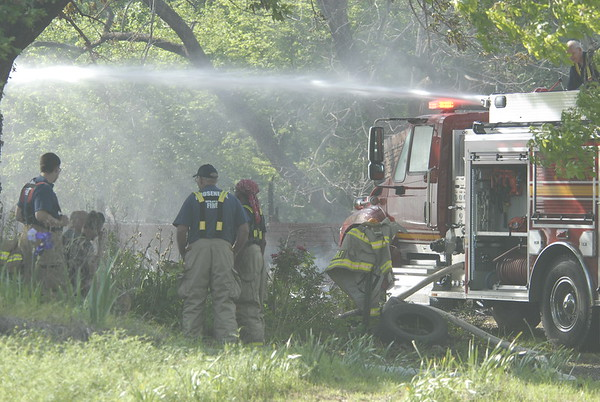 Staff photo by Wendy Burton<br /> Firefighters soak the remains of a house that burned down Wednesday in an attempt to cool things down enough for Muskogee County deputies to begin an investigation into what they believe are two bodies found in the debris.