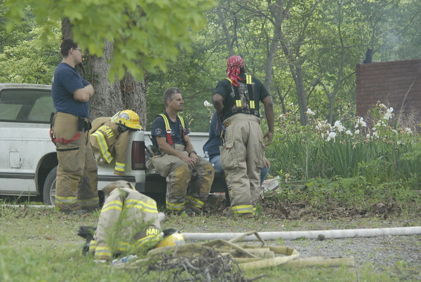 Staff photo by Wendy Burton<br /> Firefighters rest in the shade near where they spent hours putting out a house fire Wednesday. The remains of two people who have not yet been identified were found in the debris.