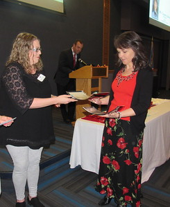 CATHY SPAULDING/Muskogee Phoenix Fort Gibson Chamber of Commerce Executive Director Jessica Fowler presents Fort Gibson High School AP teacher Cassandra Edwards with a plaque honoring her as District Teacher of the Year. The plaque was presented at the Fort Gibson Red and White Scholars Banquet.