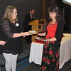 CATHY SPAULDING/Muskogee Phoenix<br /> Fort Gibson Chamber of Commerce Executive Director Jessica Fowler presents Fort Gibson High School AP teacher Cassandra Edwards with a plaque honoring her as District Teacher of the Year. The plaque was presented at the Fort Gibson Red and White Scholars Banquet.