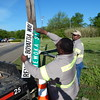 Staff photo by Mark Hughes<br /> City workers Mike Nicholson and Tony Presley attach a new street sign honoring the late Rev. R.E. Boyattia on posts Thursday along a stretch of Wewoka Street. Boyattia was the pastor of New Jerusalem Baptist Church for 20 years. The honorary street signs were placed at Wewoka and Warrior streets, 16th and Wewoka streets, and 17th and Wewoka streets.