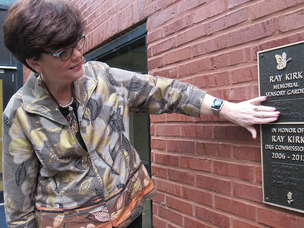 Staff photo by Cathy Spaulding<br /> Department of Rehabilitation Services Interim Director Noel Tyler feels the Braille letters on the Ray Kirk Memorial Garden dedication marker at Oklahoma School for the Blind.