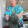 "CATHY SPAULDING/Muskogee Phoenix<br /> Polly Moore explains how she carved her soapstone<br /> sculpture, ""Wind in my Mane."" It is on display at the<br /> Muskogee Art Guild."