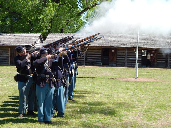 Staff photo by Mark Hughes<br /> Members of the Frontier Brigade fire off their vintage Civil War rifles at the historic Fort Gibson on Saturday. The re-enactors were the first to use the fort after a ribbon-cutting ceremony Friday opened it to the public following three years of renovation.