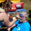 Staff photo by Mark Hughes<br /> Kimberly Quillman paints Richard Rhodes' forehead with the colors and logo of Captain America.