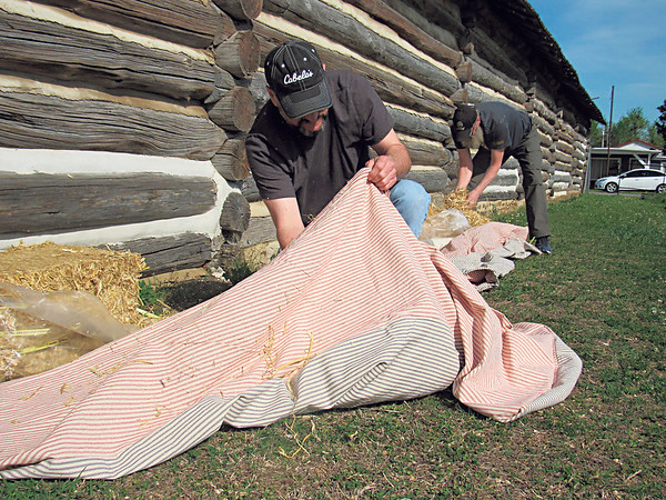 CATHY SPAULDING/Muskogee Phoenix<br /> Todd Meek, left, and Todd Reifschneider, fill their mattress ticks with straw as they prepare for the 24th Missouri Volunteer Infantry's Spring Muster at Fort Gibson Historic Site. The two Wichita, Kansas, area residents are part of the Civil War re-enactor group.