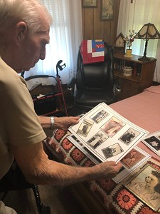 CHESLEY OXENDINE/Muskogee Phoenix William Freeman shows some of the pictures of him and his wife arranged by a friend in honor of the couple's 75th wedding anniversary.