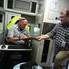 """Staff photo by Wendy Burton<br /> Brian Wood, right, brings paperwork for Paramedic James Garvin to sign after returning to the main Muskogee County Emergency Medical Service station after a call. The long-time emergency personnel are receiving special recognition at both the state and national level for being """"unsung heroes."""""""