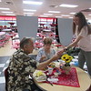 CATHY SPAULDING/Muskogee Phoenix<br /> Fort Gibson High School sophomore Lexie Foutch, left, hands salt and pepper shakers to Tom Moydell, sitting with wife Lucille Moydell, at Tuesday's annual Golden Agers Breakfast at Fort Gibson Schools' Tiger's Den cafeteria. The breakfast featured giveaways and music. Fort Gibson High School students and community volunteers and business leaders helped serve the breakfast.