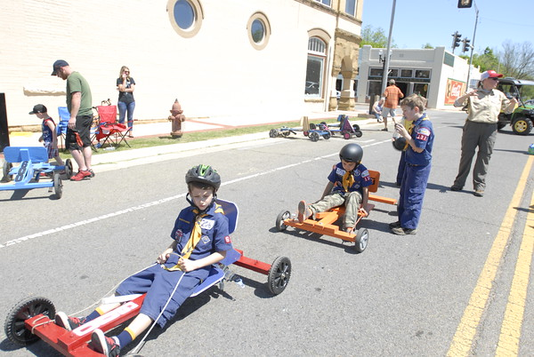 Staff photo by Cathy Spaulding<br /> Cub Scouts wait in their wooden carts before participating in Cubmobile Races on Saturday in Fort Gibson. Cubmobiles raced two abreast down Poplar Street.