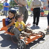Staff photo by Cathy Spaulding<br /> Tulsa Cub Scout Boston Little, 7, left, shares his Cubmobile with his 1-year-old brother, Sawyer Little, while waiting to race on Saturday morning. Boston was among dozens of Cub Scouts participating in Cubmobile Races.