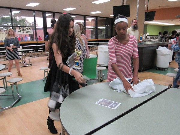 Staff photo by Cathy Spaulding<br /> Whittier Elementary student Destiny Bias, left, holds her character award while helping Muskogee High School student Cierra Lewis clear tables after Tuesday's Muskogee Public Schools Character Banquet.