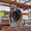 CATHY SPAULDING/Muskogee Phoenix<br /> Catholic Charities volunteer Bill Todd stocks canned vegetables in the food pantry. The pantry has seen an increase in new clients over the past few weeks.