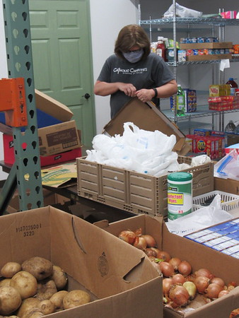 CATHY SPAULDING/Muskogee Phoenix<br /> Catholic Charities volunteer Mary Upchurch wears a mask while flattening boxes in the ministry's food pantry.