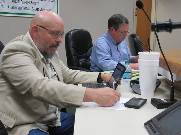 Staff photo by Cathy Spaulding<br /> Bobby Jefferson, left, takes notes on a Muskogee Board of Education meeting agenda Tuesday night before being sworn in as Office 1 member of the board. Next to him is board president Mike Ebert.