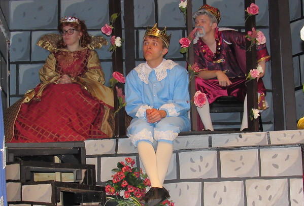 """Staff photo by Cathy Spaulding<br /> Prince Dauntless (Ethan Burk, center) waits on an appropriate suitor while domineering mother Queen Aggravain (Mattie Hurlburt) and King Sextimus (Haven Gulley) watch. Hilldale High School tells the tale<br /> in the musical """"Once Upon a Mattress."""""""