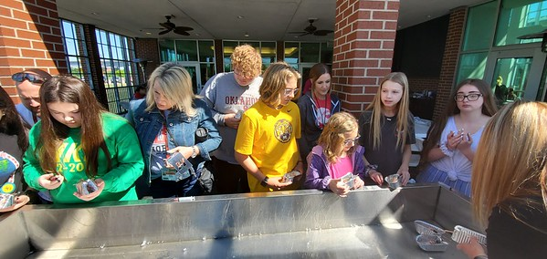 CHESLEY OXENDINE/Muskogee Phoenix<br /> Students gather around a small trough for the mock voyage of their miniature steamboats, constructed with tiny foil trays and copper coils during Manufacturing Block Day Party, hosted by Muskogee Dream It. Do it. at the River Center at Three Forks Harbor on Friday.