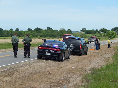 Staff photo by Wendy Burton A Oklahoma Highway Patrol troopers investigate the scene where a Warner woman was killed and two others injured in a head-on wreck Thursday.